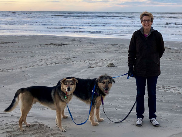 Nancy Bader on beach with two dogs
