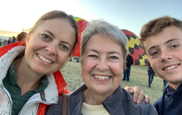 two women and a boy in front of hot air balloons